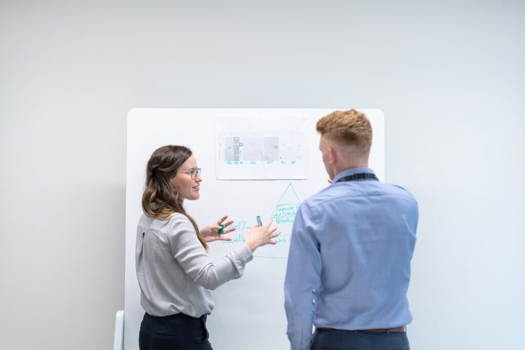 Two people standing in front of whiteboard discussing something.
